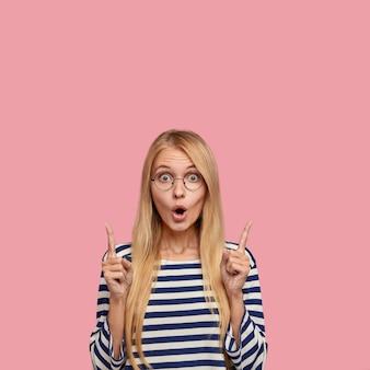 Femme aux cheveux clairs surpris émotionnelle regarde avec des yeux buggés, se sent impressionnée par quelque chose