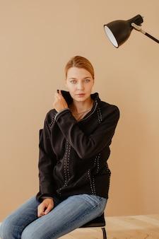 Femme aux cheveux courts sur une chaise devant la lumière du studio