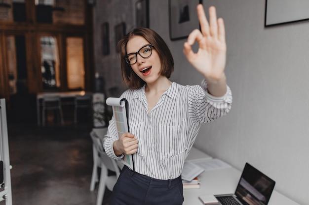 Femme aux cheveux courts en chemisier rayé montre le signe ok. portrait de femme ouvrière dans des verres en clignant des yeux et s'appuyant sur la table avec ordinateur portable