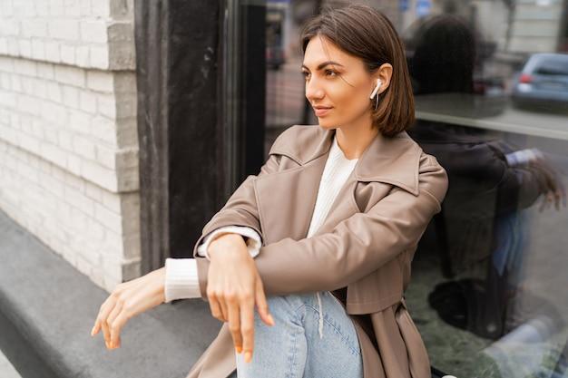 Femme aux cheveux courts confiante portant un manteau de couleur beige à la mode et un sac à bandoulière en cuir texturé blanc, marchant dans la rue de la ville européenne