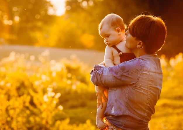 Femme aux cheveux courts embrasse son enfant debout sur la pelouse dans la soirée