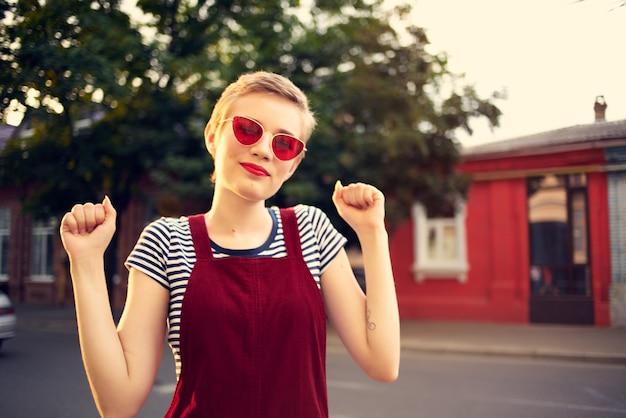 Femme aux cheveux courts à l'extérieur portant des lunettes de soleil mode promenade d'été