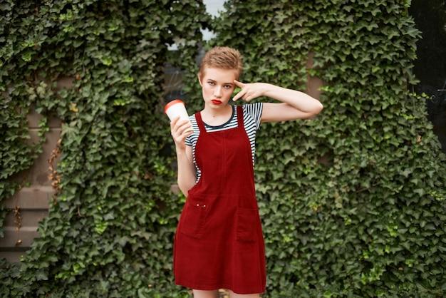 Femme aux cheveux courts à l'extérieur une tasse d'arbustes de style de vie de boisson