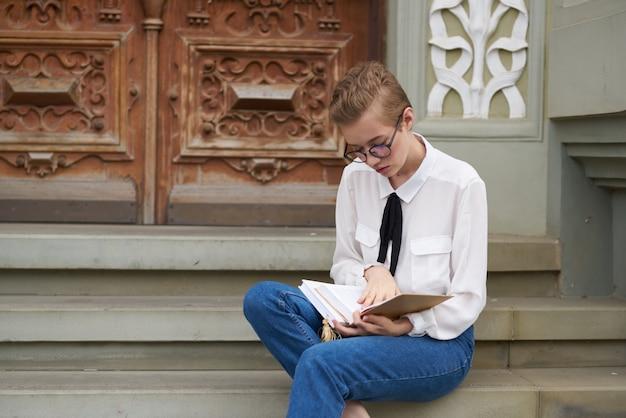 Femme aux cheveux courts avec un livre dans ses mains à l'extérieur de la communication de lecture