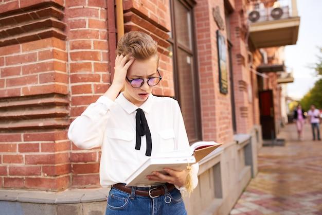 Femme aux cheveux courts avec un livre dans ses mains en plein air style de lecture