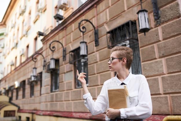 Femme aux cheveux courts avec des lunettes se promenant dans la ville avec un style de vie de livre