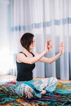 Femme aux cheveux courts méditant avec le geste de gyan mudra