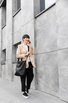 Femme aux cheveux courts parlant au téléphone à l'extérieur