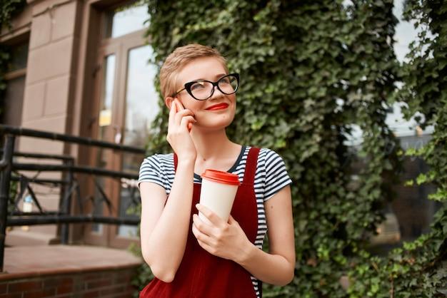 Femme aux cheveux courts portant des lunettes dans la rue parlant au téléphone tasse de café