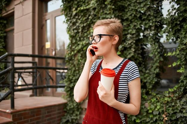 Femme aux cheveux courts portant des lunettes dans la rue parlant au téléphone