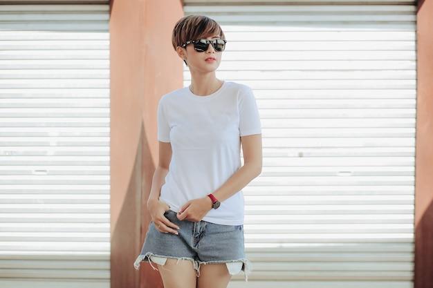 Femme aux cheveux courts portant un t-shirt blanc et un pantalon court avec des lunettes de soleil