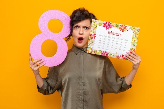 Femme aux cheveux courts tenant le calendrier papier du mois de mars et le numéro huit à la fois confus et mécontent de célébrer la journée internationale de la femme le 8 mars