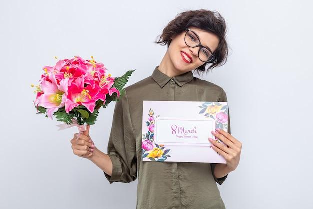 Femme aux cheveux courts tenant une carte de voeux et un bouquet de fleurs à la recherche de sourires célébrant joyeusement la journée internationale de la femme le 8 mars
