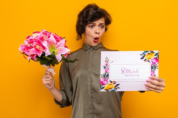 Femme aux cheveux courts tenant une carte de voeux et un bouquet de fleurs regardant la carte confuse et surprise célébrant la journée internationale de la femme le 8 mars