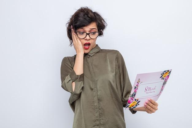 Femme aux cheveux courts tenant une carte de voeux la regardant confuse et surprise célébrant la journée internationale de la femme le 8 mars