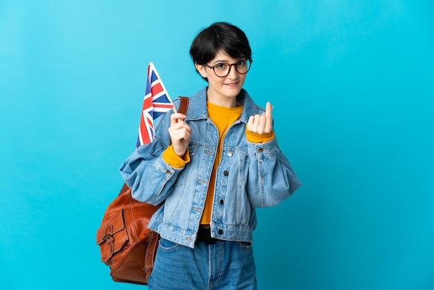 Femme aux cheveux courts tenant un drapeau du royaume-uni isolé sur l'espace bleu faisant le geste de l'argent
