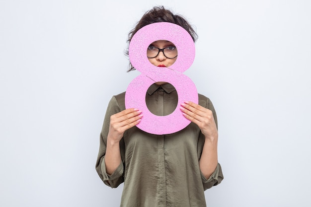 Femme aux cheveux courts tenant le numéro huit regardant à travers ce numéro célébrant la journée internationale de la femme le 8 mars