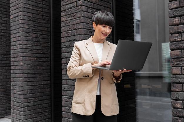 Femme aux cheveux courts vérifiant son ordinateur portable