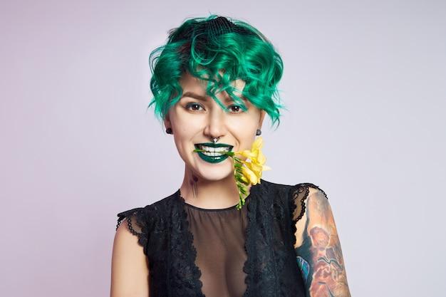 Femme aux cheveux créatifs et coloration verte créative, mèches de cheveux toxiques.