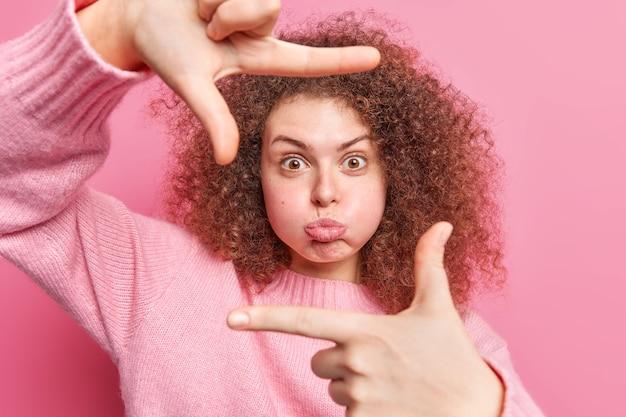 Une femme aux cheveux cury drôle souffle les joues fait que le cadre de la main essaie de capturer le moment vêtu de poses de cavalier décontractées contre des plans muraux roses la position parfaite mesure l'angle des images quelque chose.
