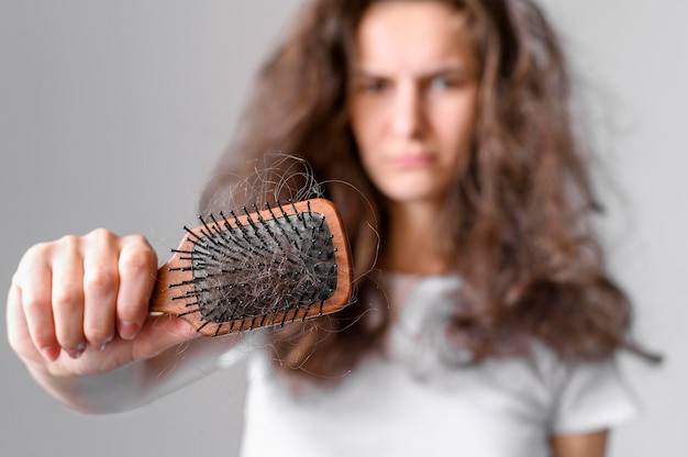 Femme aux cheveux emmêlés et brosse