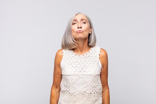 Femme aux cheveux gris en appuyant sur les lèvres avec une expression mignonne