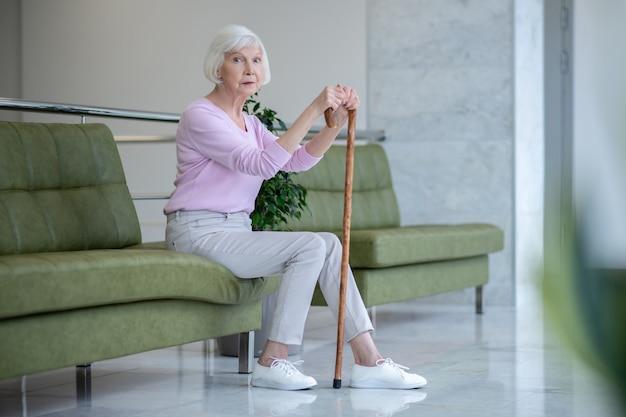 Femme aux cheveux gris avec un bâton de marche assis dans le couloir et à la sérieuse