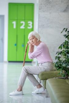 Femme aux cheveux gris avec un bâton de marche assis dans le couloir