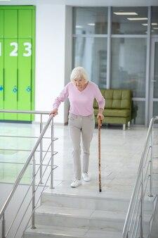 Femme aux cheveux gris avec un bâton de marche en descendant
