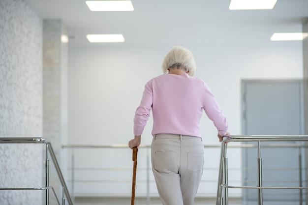 Femme aux cheveux gris avec un bâton de marche à l'étage