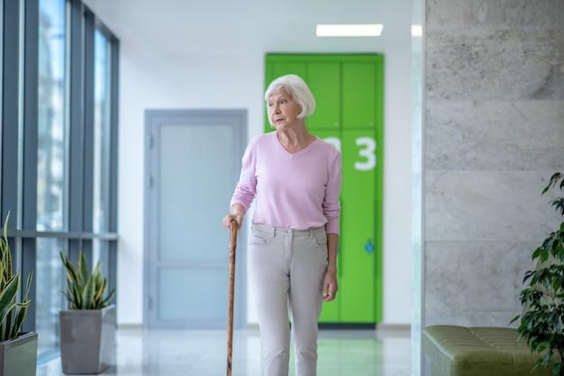 Femme aux cheveux gris avec un bâton de marche marchant dans le couloir