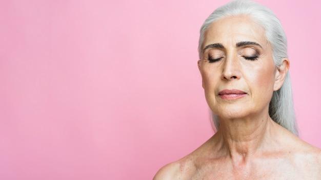 Femme aux cheveux gris sur fond rose