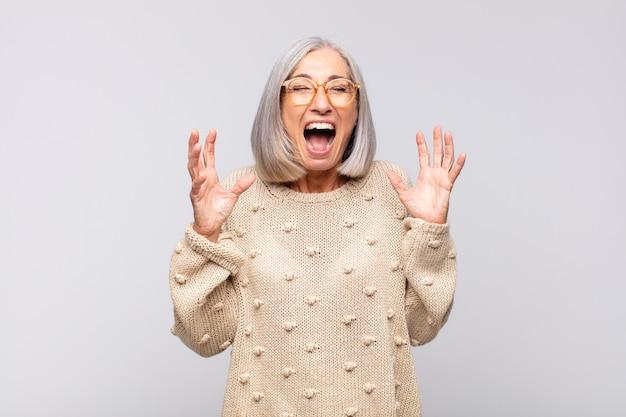 Femme aux cheveux gris hurlant furieusement, se sentant stressée et agacée avec les mains en l'air en disant pourquoi moi