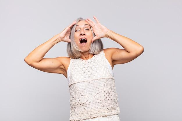 Femme aux cheveux gris levant les mains à la tête, bouche bée, se sentant extrêmement chanceuse, surprise, excitée et heureuse