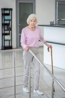 Femme aux cheveux gris marche avec un bâton de marche