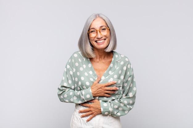 Femme aux cheveux gris riant à haute voix à une blague hilarante, se sentir heureux et joyeux, s'amuser