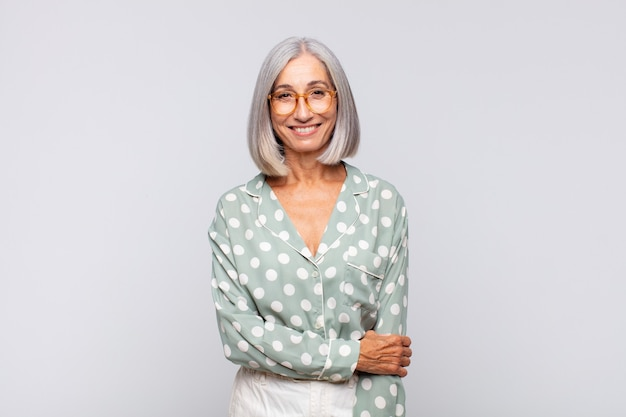 Femme aux cheveux gris riant timidement et joyeusement, avec une attitude amicale et positive mais peu sûre