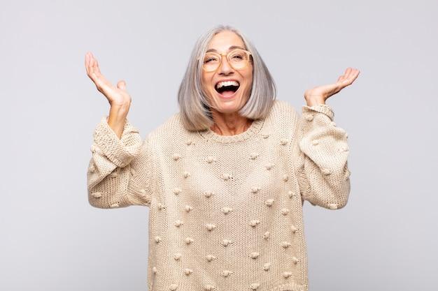 Femme aux cheveux gris se sentant heureuse, étonnée, chanceuse et surprise, célébrant la victoire avec les deux mains en l'air