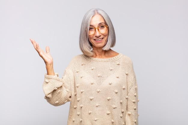 Femme aux cheveux gris se sentant heureuse, surprise et joyeuse, souriante avec une attitude positive, réalisant une solution ou une idée