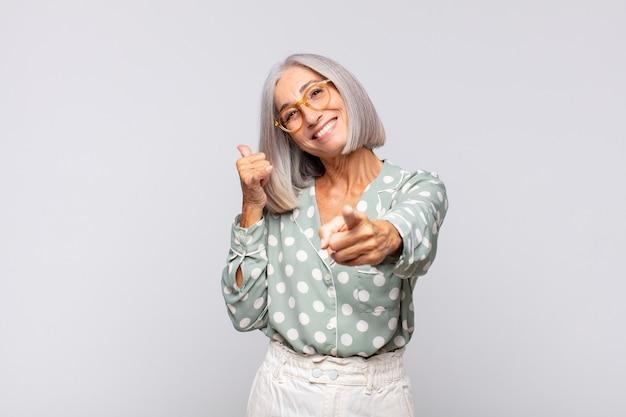 Femme aux cheveux gris souriant joyeusement et pointant