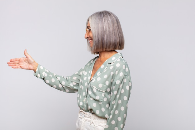 Femme aux cheveux gris souriant, vous saluant et vous offrant une poignée de main