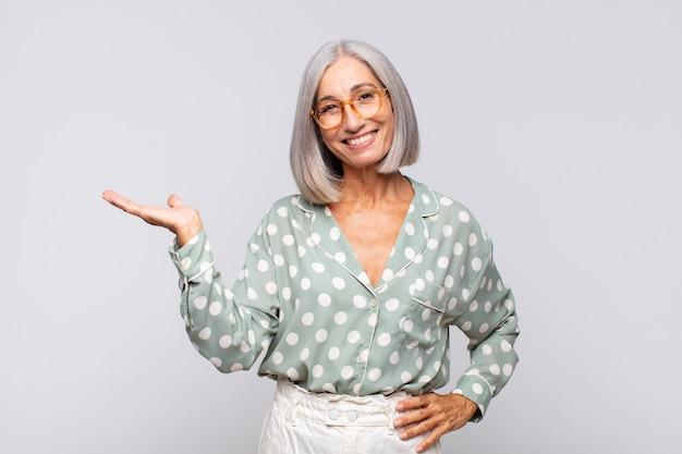 Femme aux cheveux gris souriante, confiante, réussie et heureuse, montrant un concept ou une idée sur l'espace de copie sur le côté