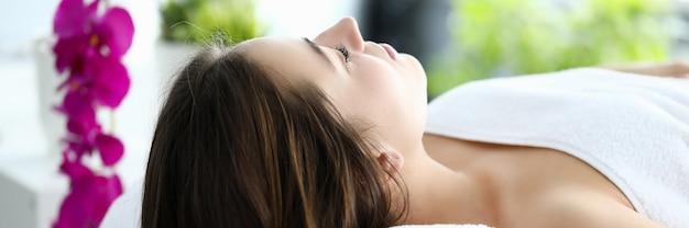 Femme aux cheveux longs allongé sur le dos sur une table de massage avec les yeux fermés