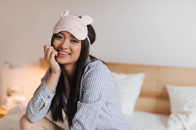 Femme aux cheveux longs aux yeux bruns en pyjama bleu et masque de sommeil s'est penchée et sourit doucement