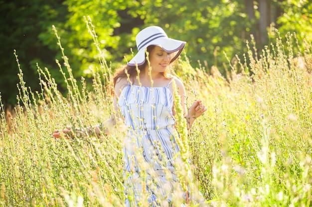 Femme aux cheveux longs en chapeau et robe marchant à travers la forêt d'été par une journée ensoleillée