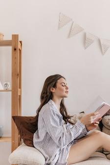Femme aux cheveux longs en chemise bleue est assise sur un canapé et lit un livre