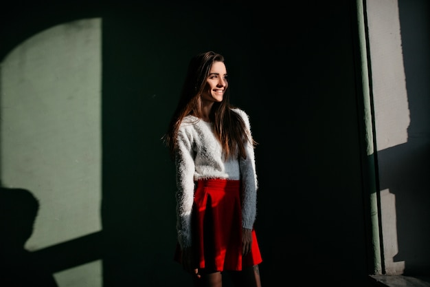 Femme aux cheveux longs pensif exprimant happines lors d'une séance photo en intérieur