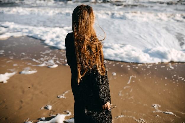Femme aux cheveux longs, portant un manteau, debout au bord de la mer, regardant des vagues mousseuses