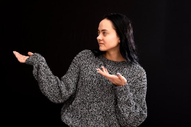 Femme aux cheveux longs portant un pull gris gesticulant avec ses mains