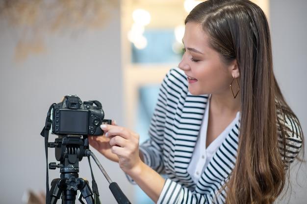 Femme aux cheveux longs positive en appuyant sur un bouton de la caméra en se tenant debout pour enregistrer une vidéo